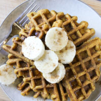 Overhead view of pumpkin waffles on gray plate topped with banana slices, cinnamon sprinkles, and syrup
