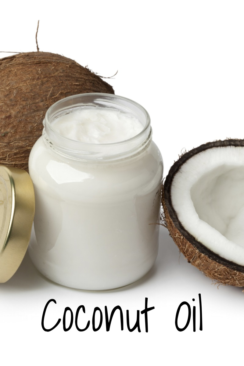 jar of coconut oil with two coconuts next to it