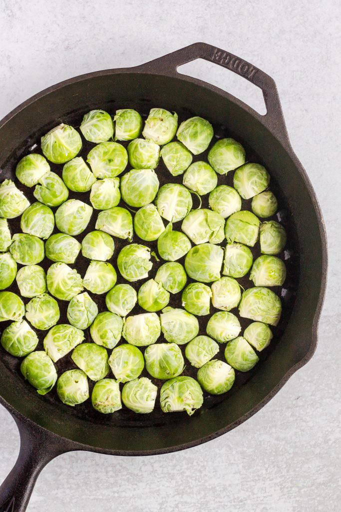 overhead view of raw brussels sprouts in case iron skillet