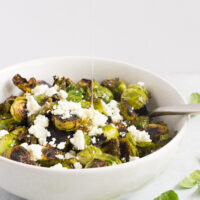 brussels sprouts in white bowl with goat cheese and honey drizzled on top