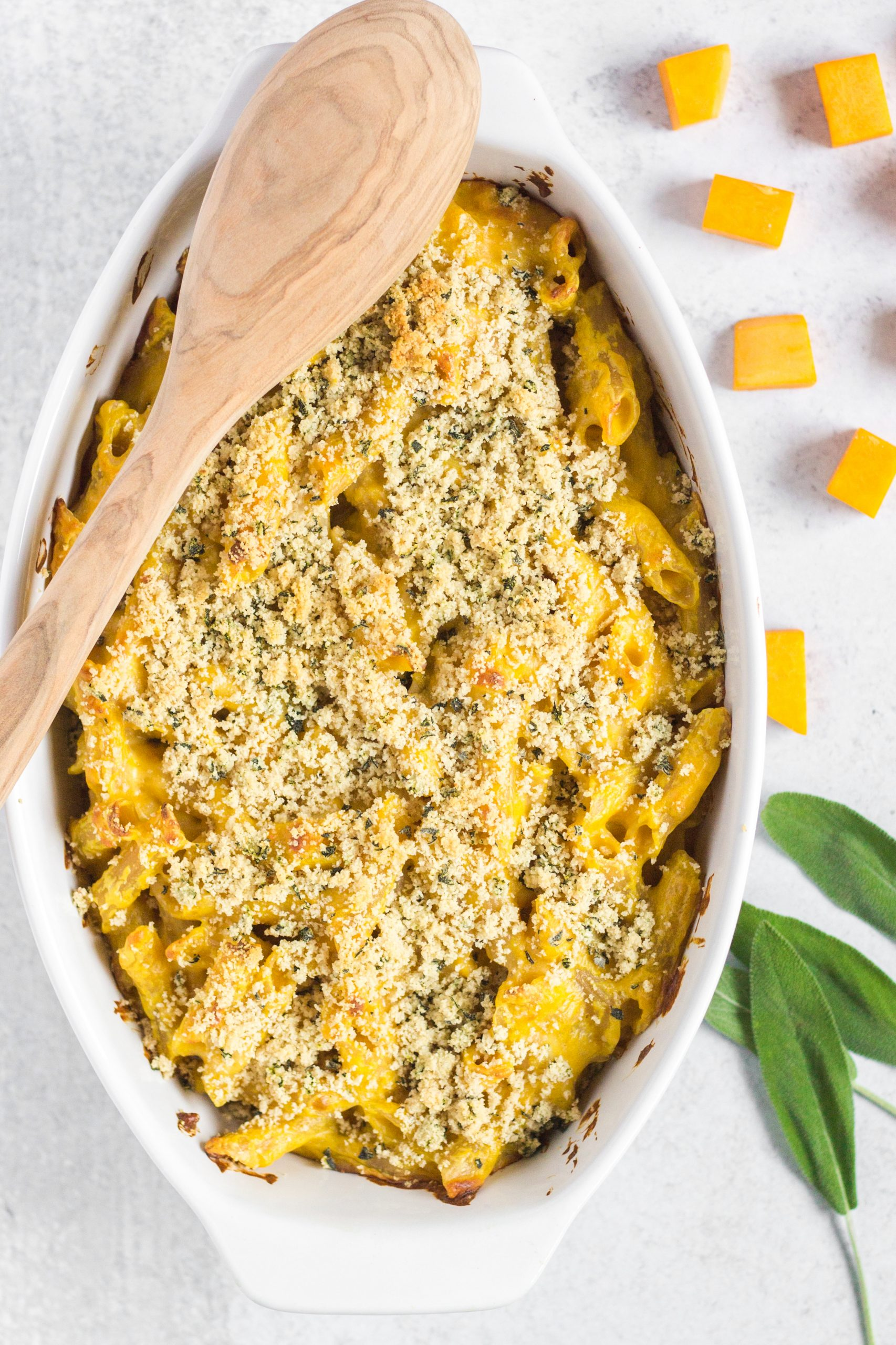 butternut squash mac and cheese in white serving dish with wooden spoon