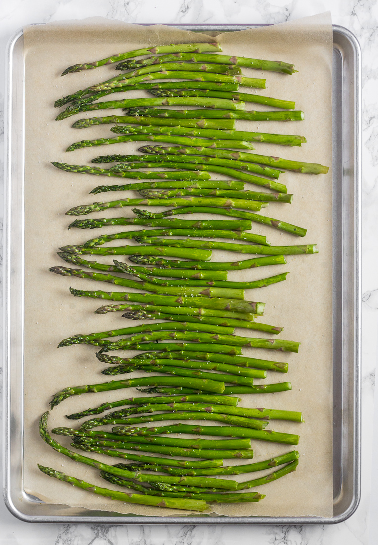 raw asparagus spears on baking sheet