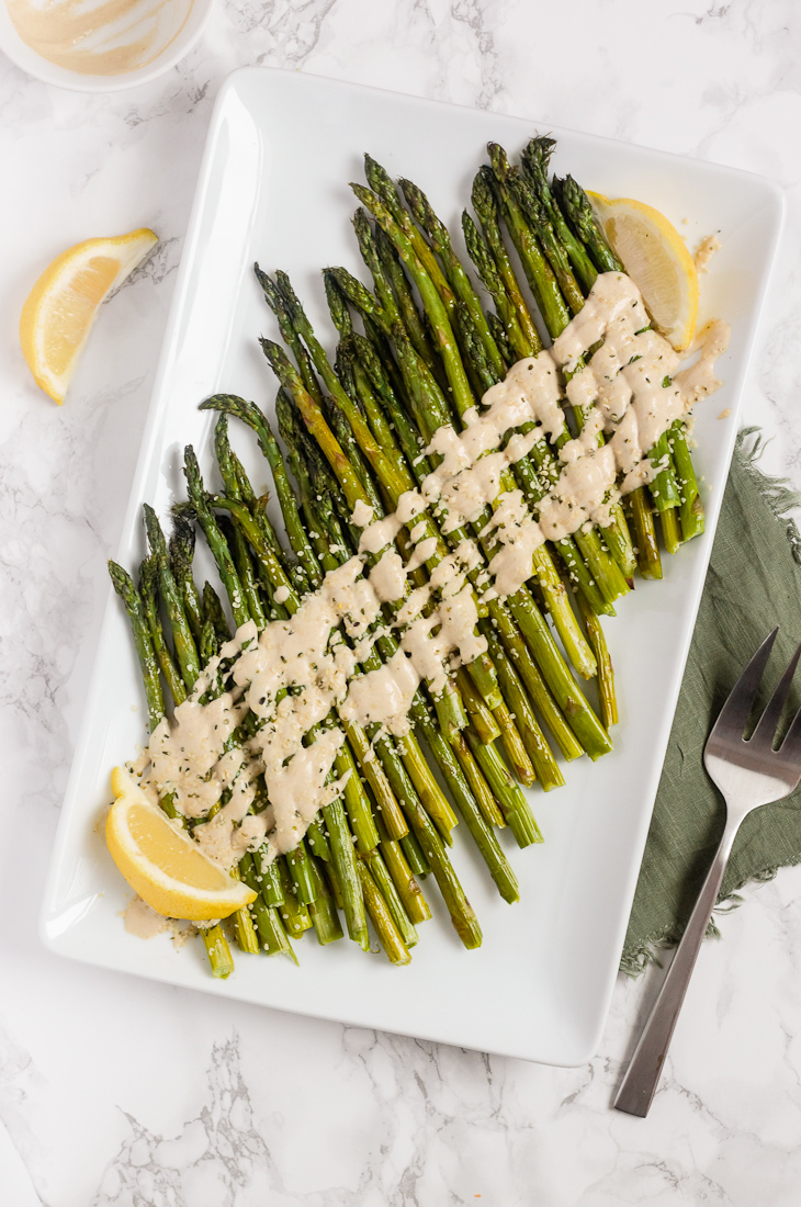 roasted asparagus with tahini on white serving plate