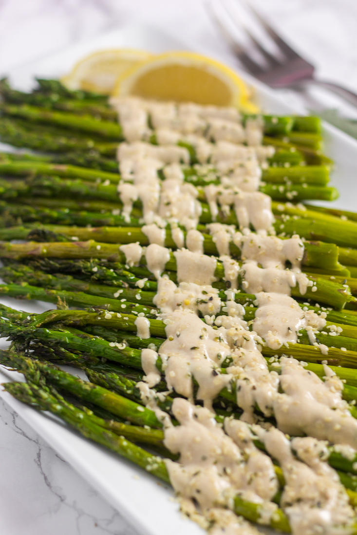 close up side view of roasted asparagus spears drizzled with tahini