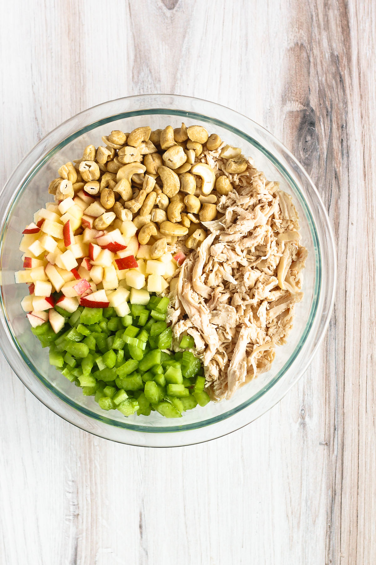 cashews, pulled chicken, apples, and celery in a mixing bowl