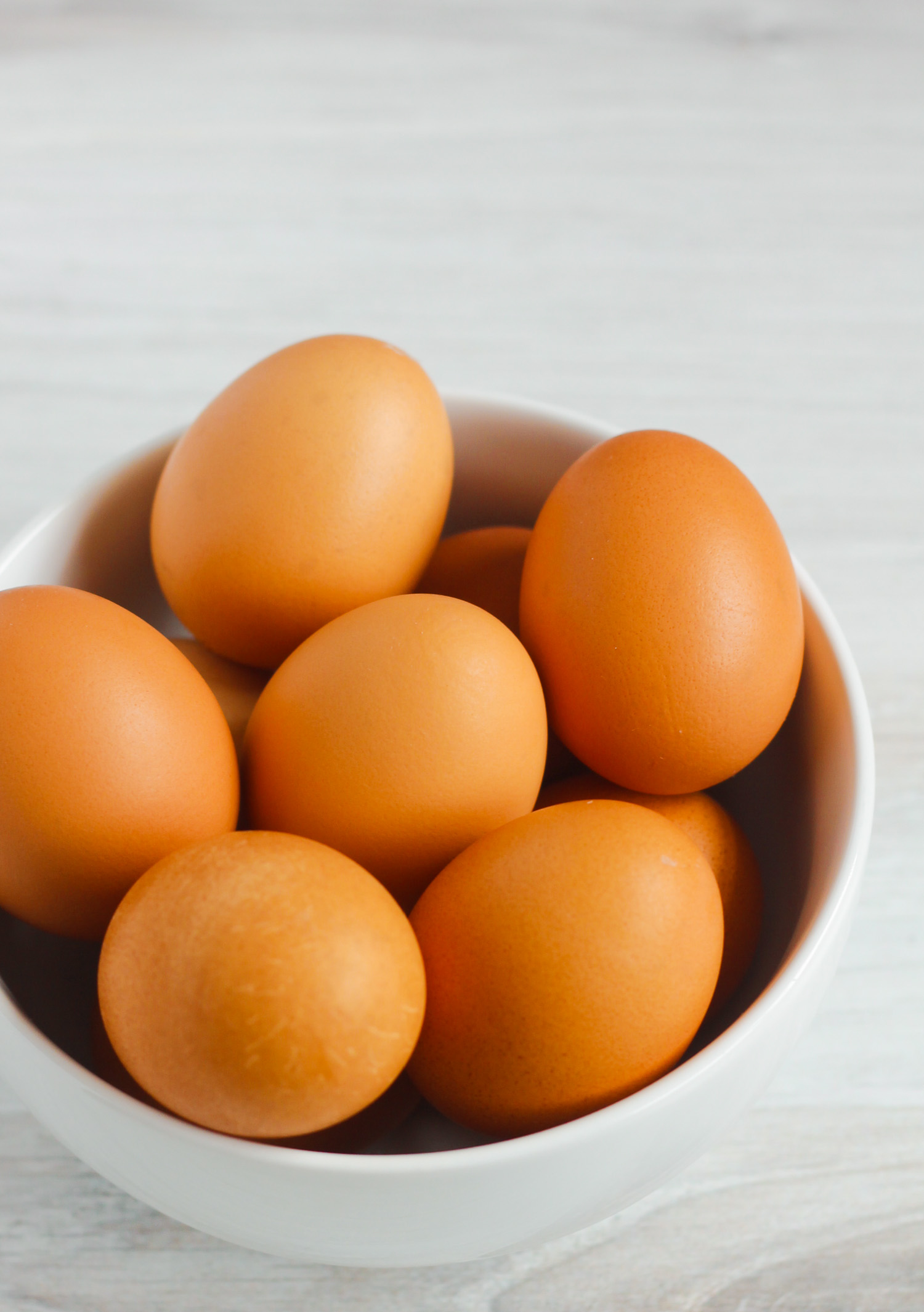 side view of brown eggs in white bowl