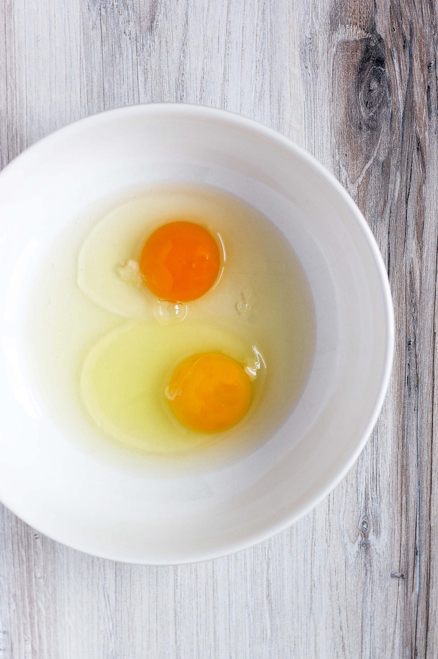 2 cracked eggs in a white bowl - one yolk is brighter orange
