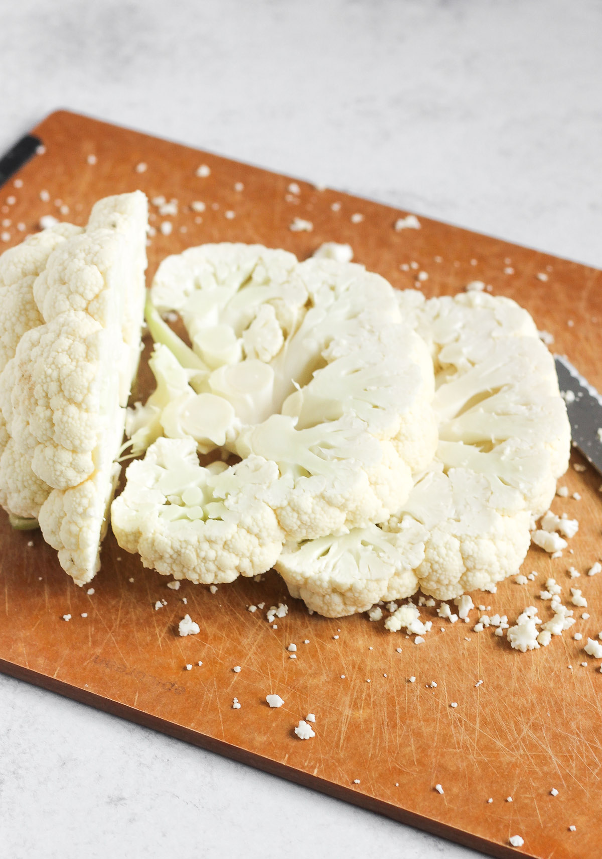 raw cauliflower head being sliced on a cutting board