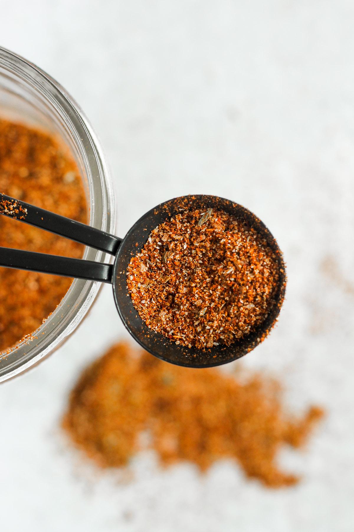 overhead view of homemade taco seasoning recipe in black teaspoon