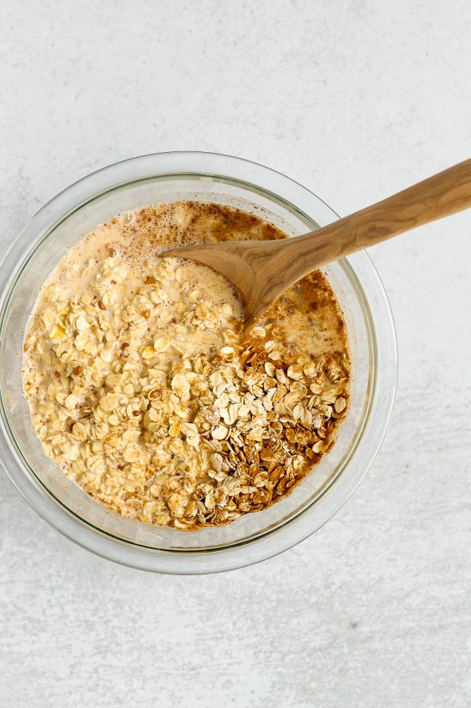 overhead view of oats and spices mixed with milk/eggs in glass mixing bowl