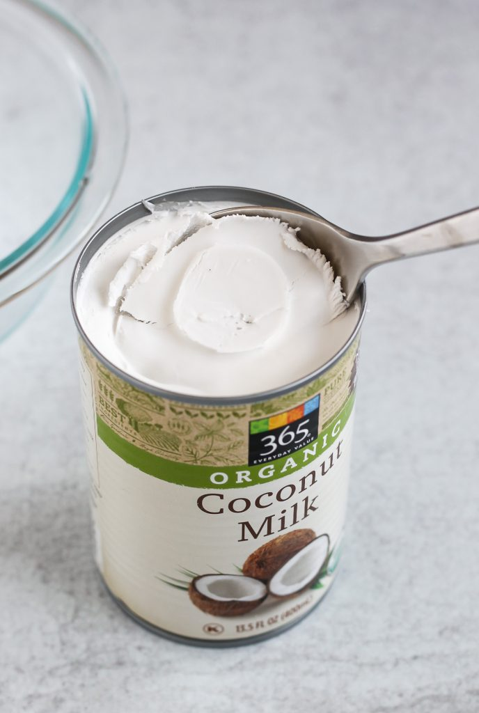 close up coconut milk can with the coconut cream being scooped out