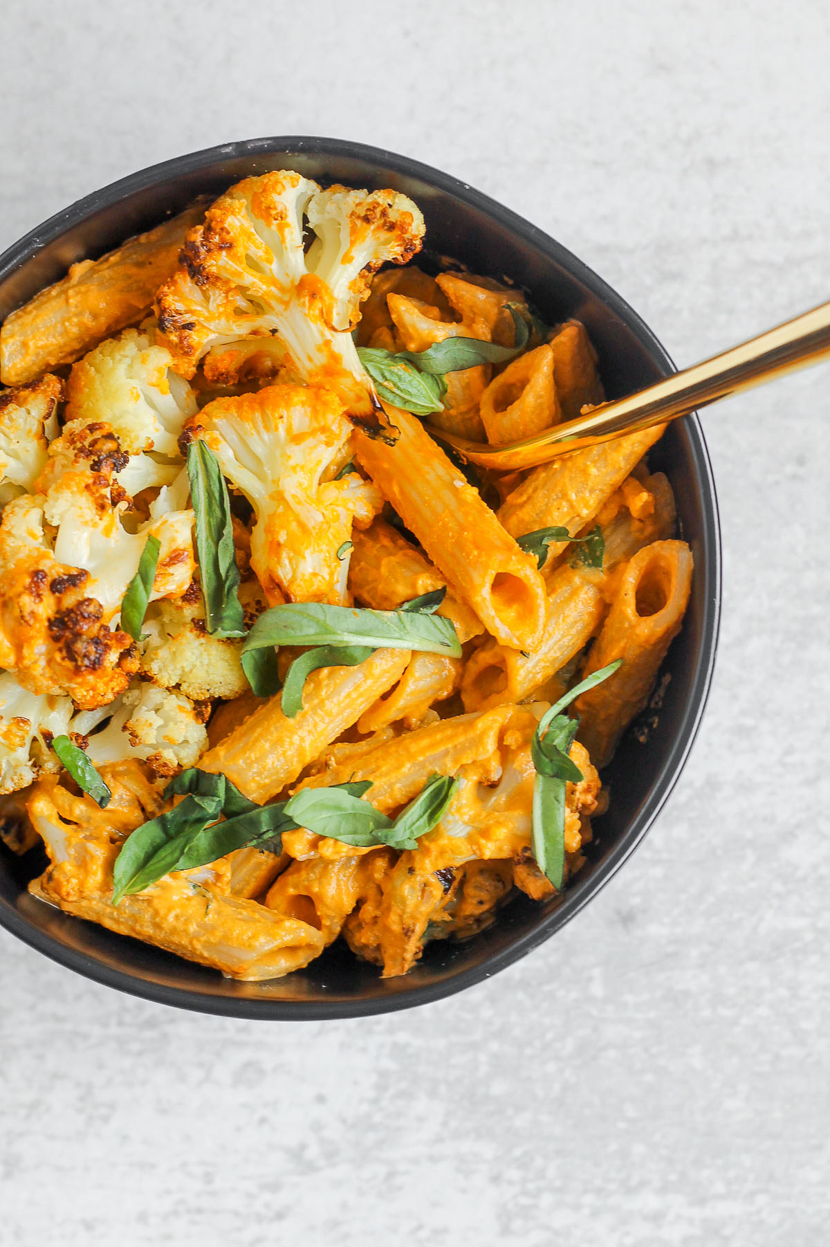 close up of penne and roasted cauliflower mixed with dairy-free roasted red pepper sauce