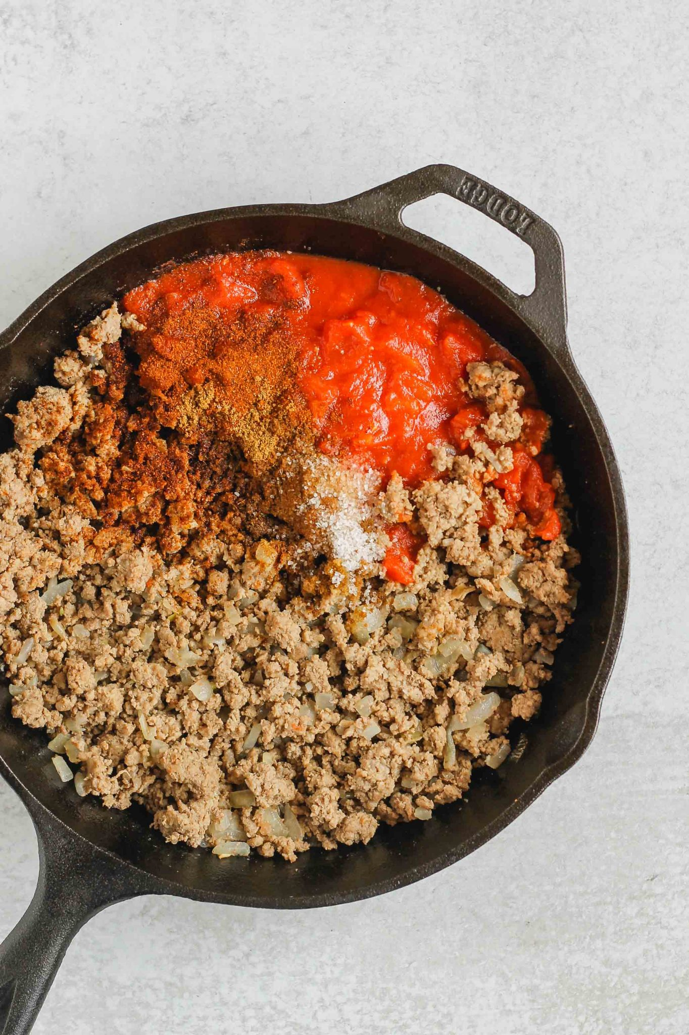 cooked ground beef, seasoning, and tomatoes in cast iron skillet before being mixed together