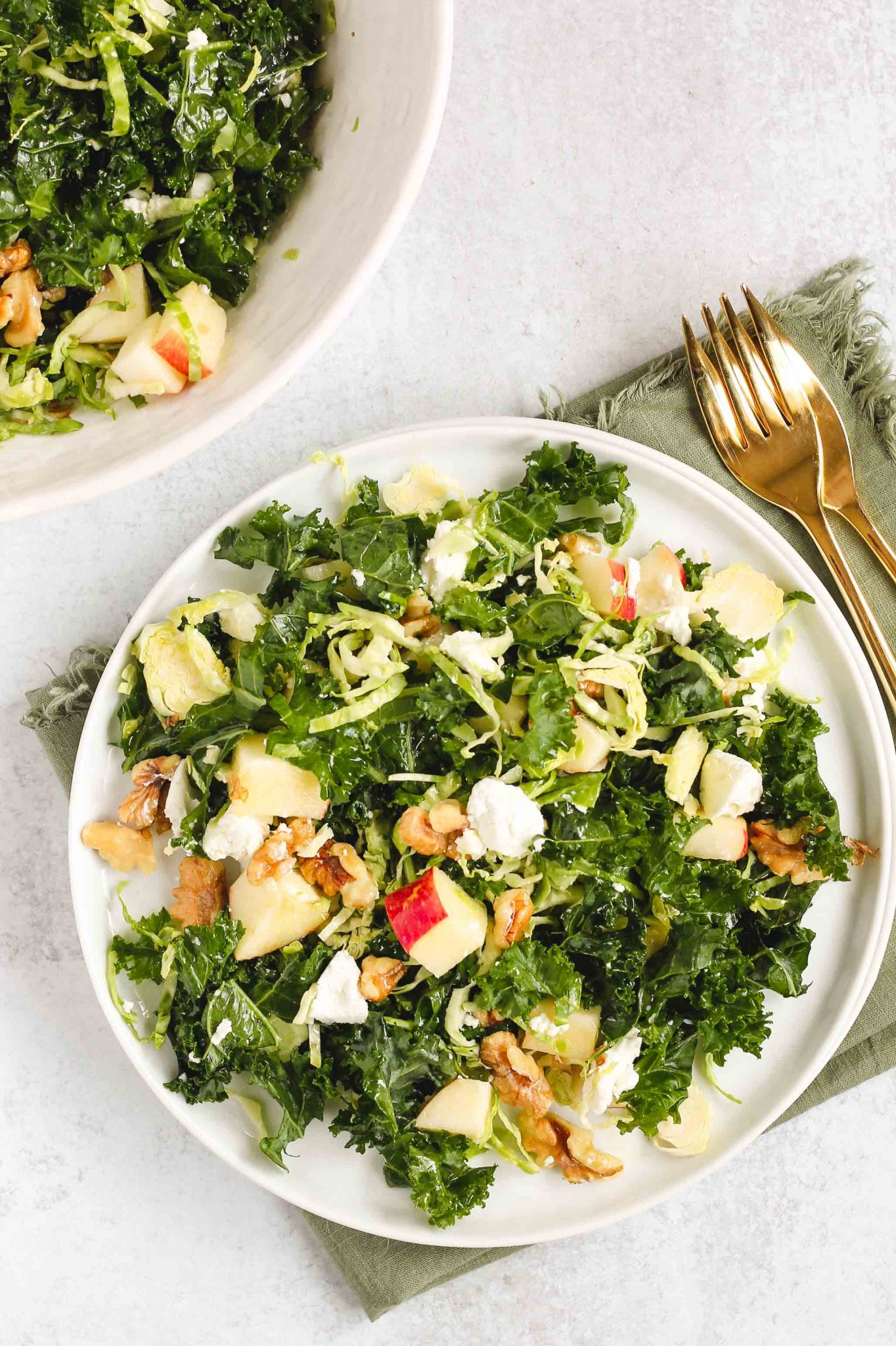 kale salad on white serving plate with gold forks