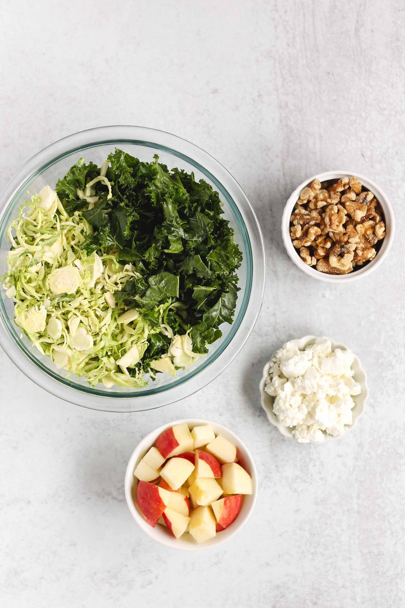 separate bowls filled with apples, goat cheese, walnuts, and Brussels sprouts and kale