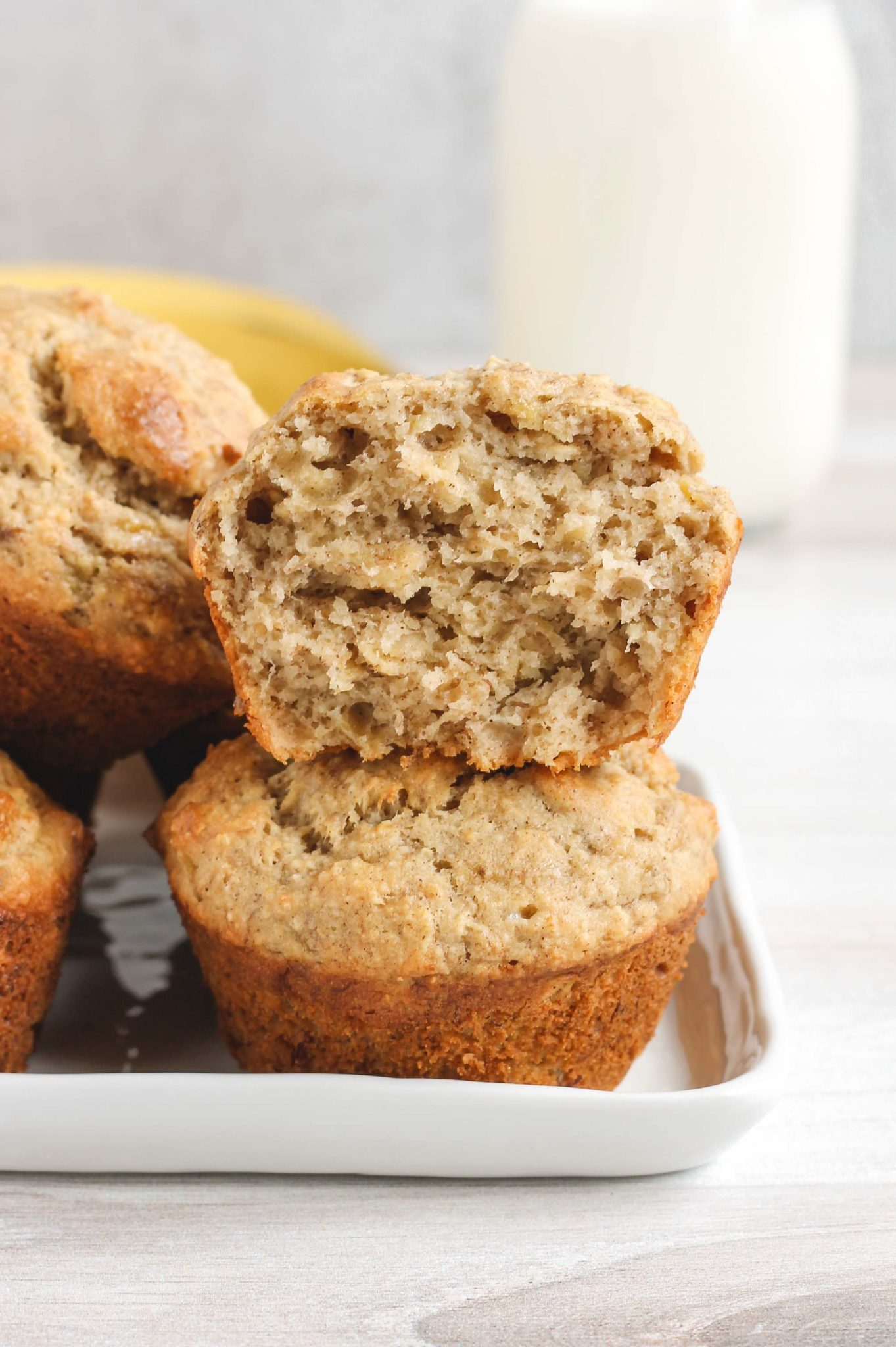 banana muffins stacked two high with top one split open to see the inside of the muffin