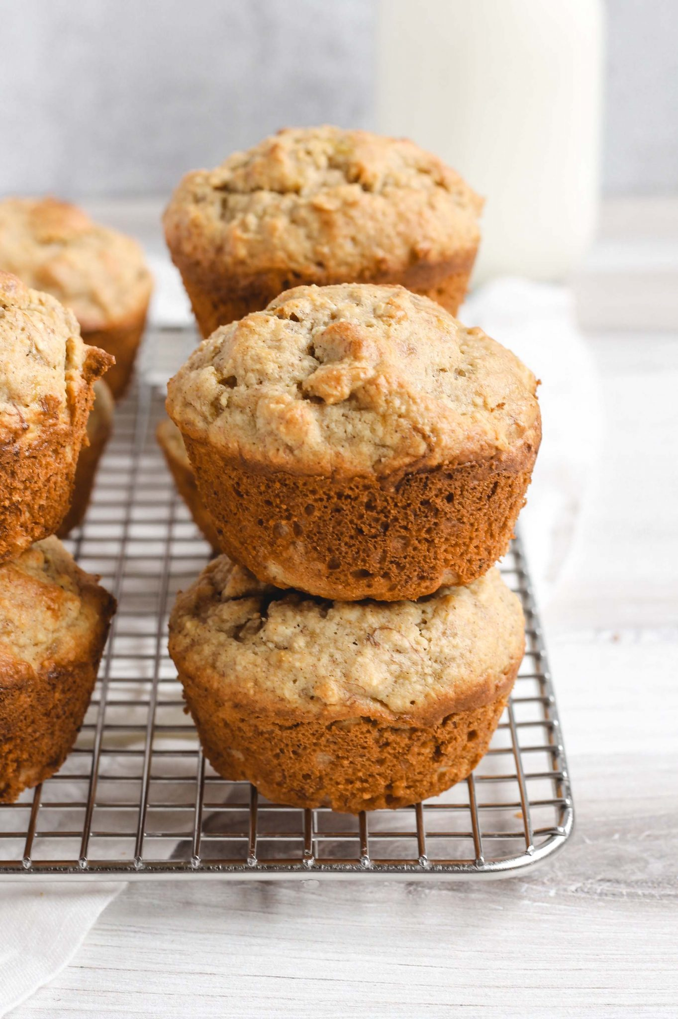 banana muffins stacked two high on a wire cooling rack