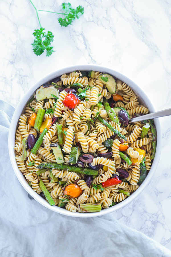 grilled vegetable pasta salad in large round serving bowl with spoon