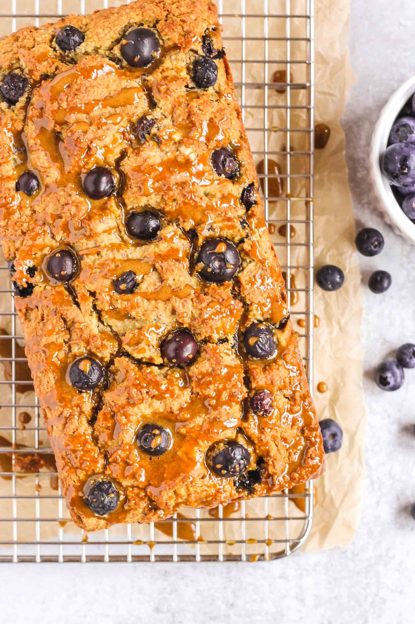 blueberry lemon bread on a wire cooling rack with blueberries sprinkled around