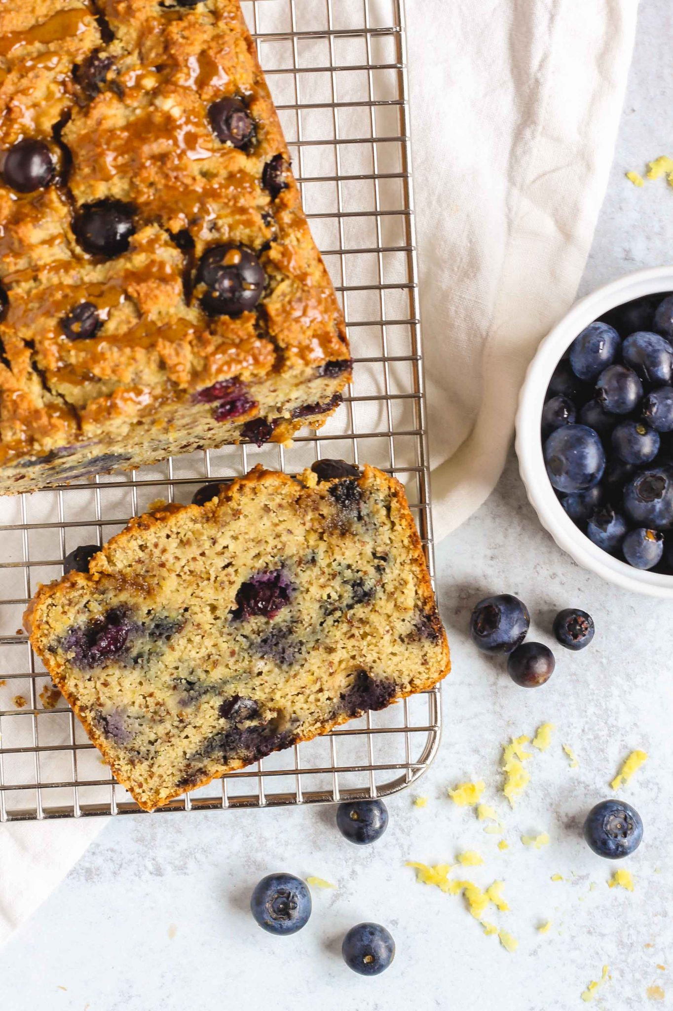 sliced lemon loaf on a wire cooling rack with blueberries sprinkled around