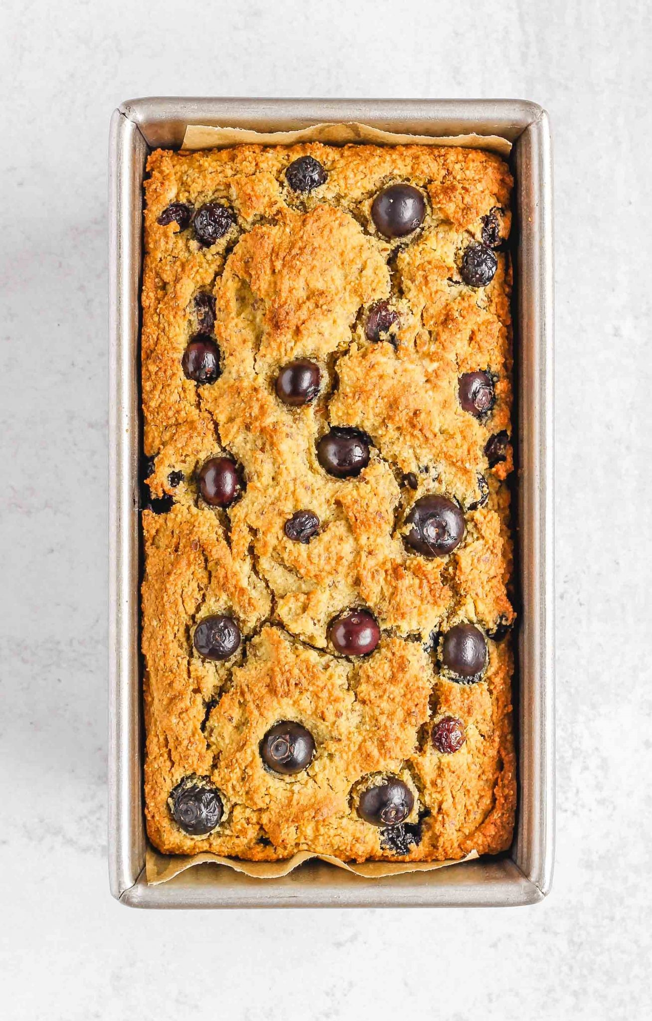 cooked almond flour blueberry bread in a tin bread loaf