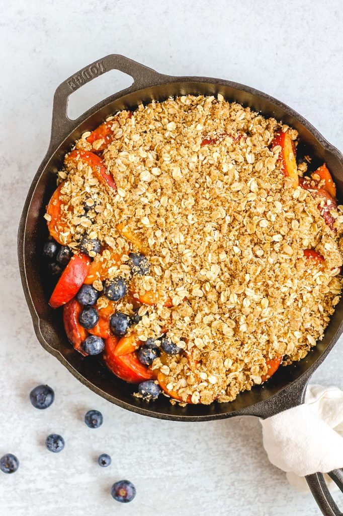 peach and blueberry crisp in cast iron skillet prior to baking
