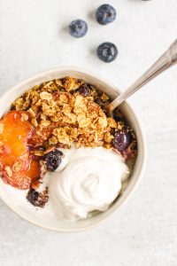 overhead view of peach and blueberry crisp in white bowl topped with coconut whipped cream