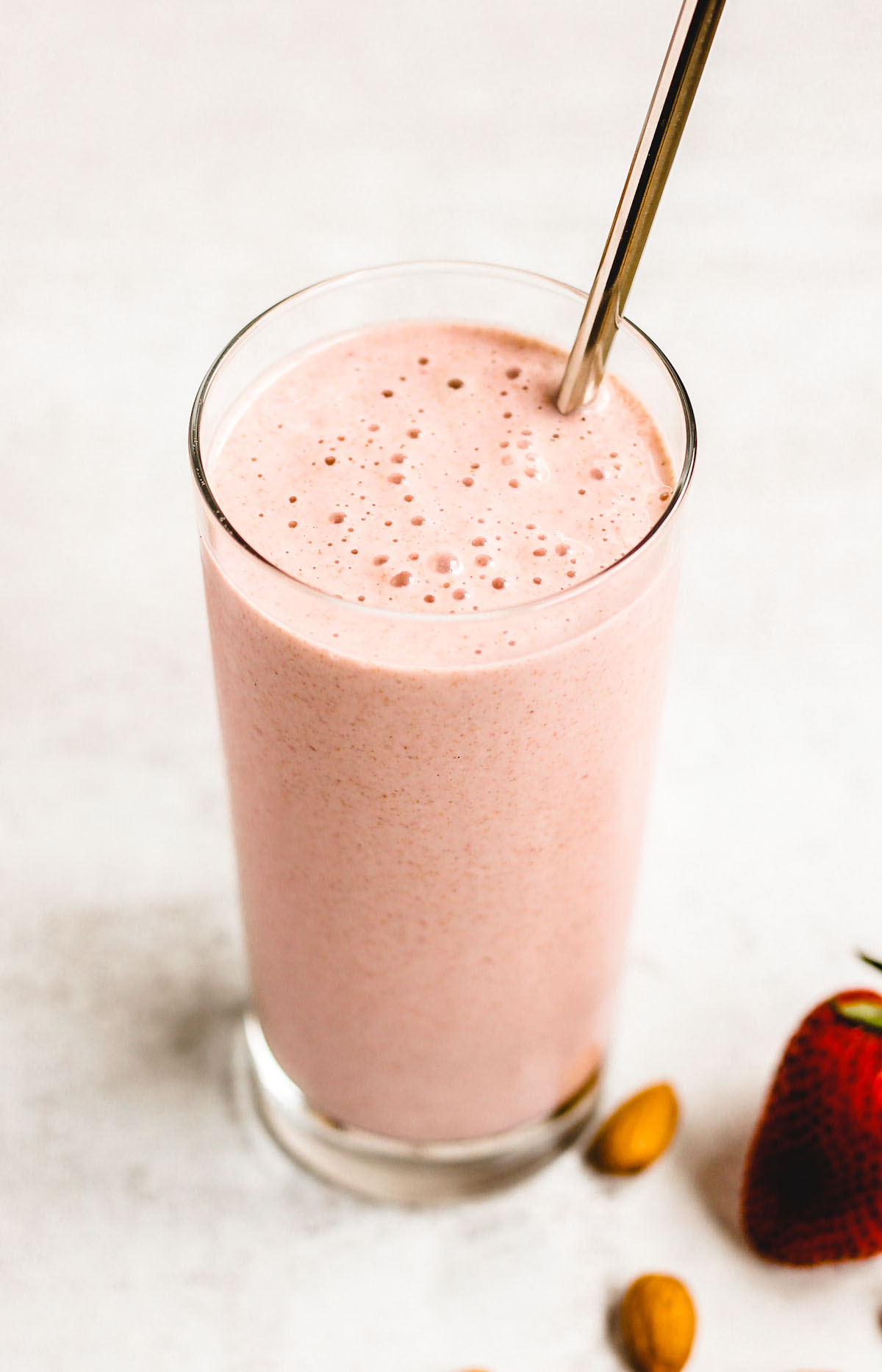 side angle view of strawberry almond smoothie in a glass with a stainless steel straw