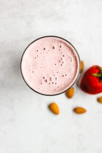 overhead view of strawberry almond smoothie in a glass