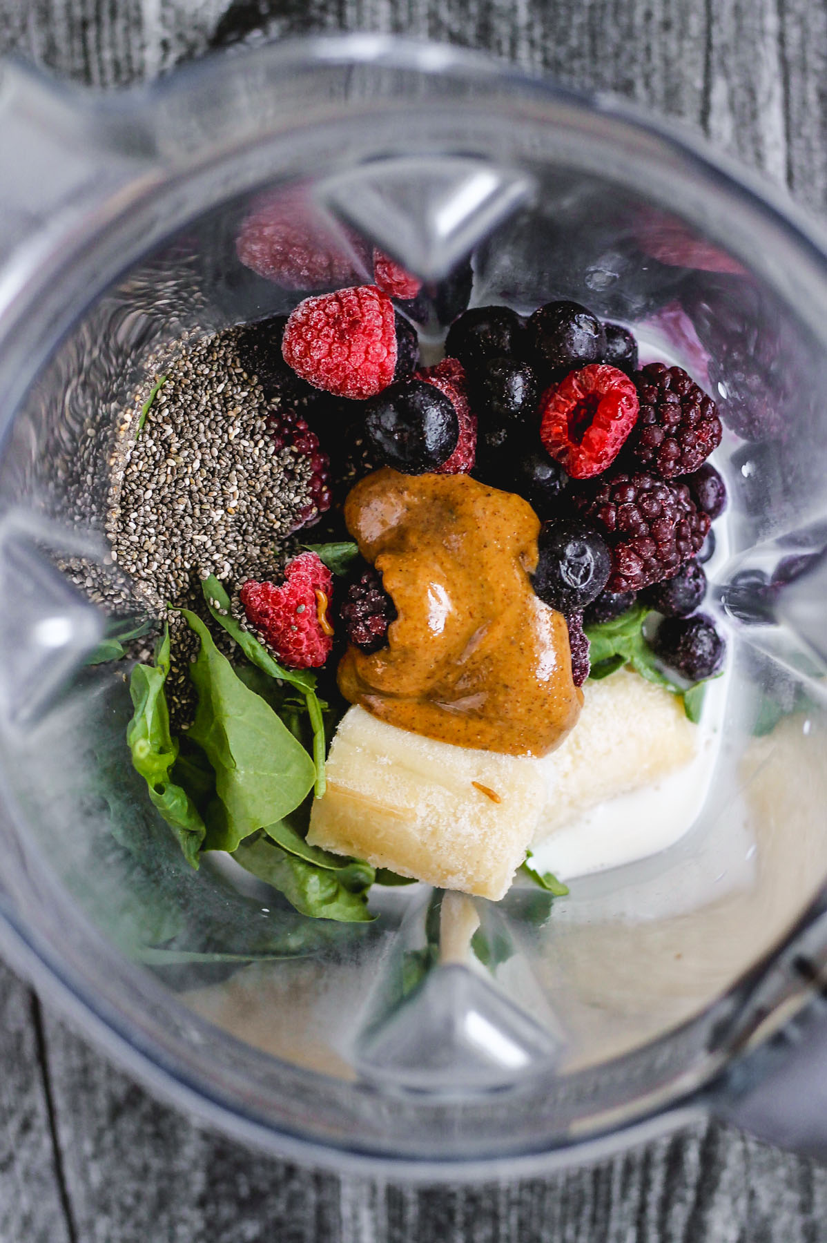 chia seeds, spinach, banana, almond butter, frozen mixed berries, and almond milk in blender before being blended