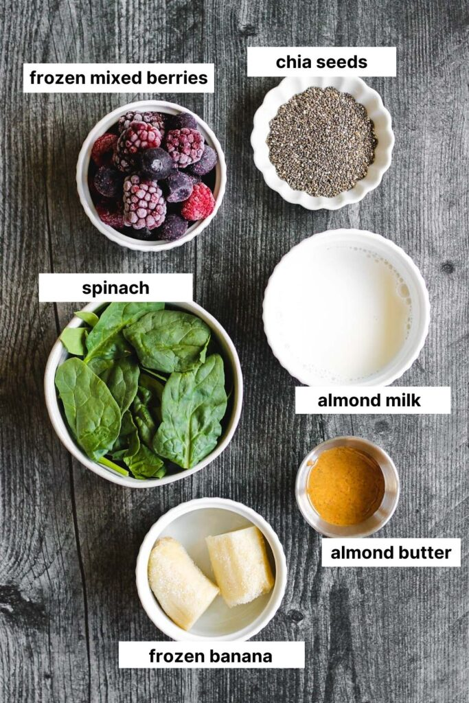 overhead view of ingredients used in this smoothie (frozen berries, chia seeds, spinach, almond milk, almond butter, frozen banana)