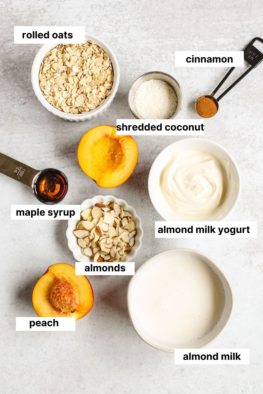 labeled ingredients needed to make peaches and cream overnight oats (oats, cinnamon, shredded coconut, maple syrup, almonds, almond milk yogurt, peach, almond milk).