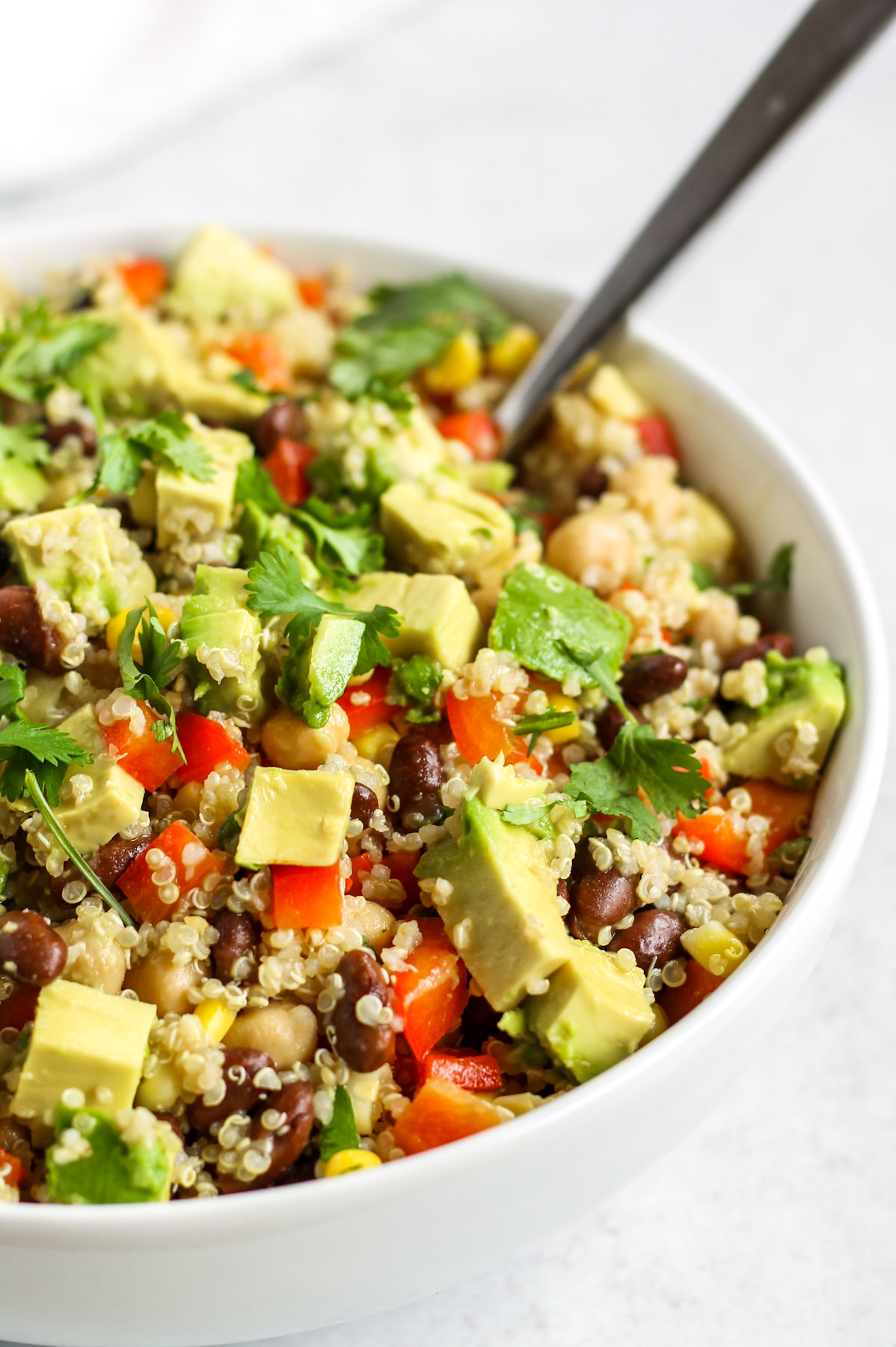 close up side view of quinoa salad in white bowl
