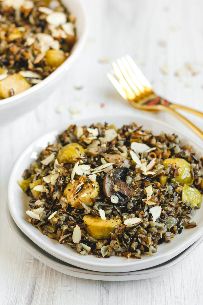 angled side view of wild rice pilaf on a small salad plate with two gold forks behind the plate
