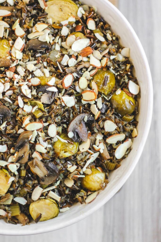 close up view of cooked wild rice pilaf in large white serving bowl