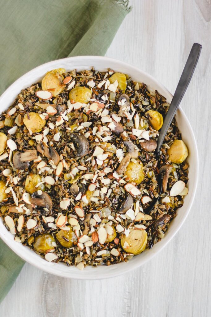 overhead view of finished pilaf in large serving bowl sprinkled with sliced almonds
