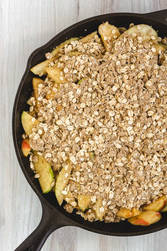 overhead view of sliced apples and crumb topping in cast iron skillet prior to being baked