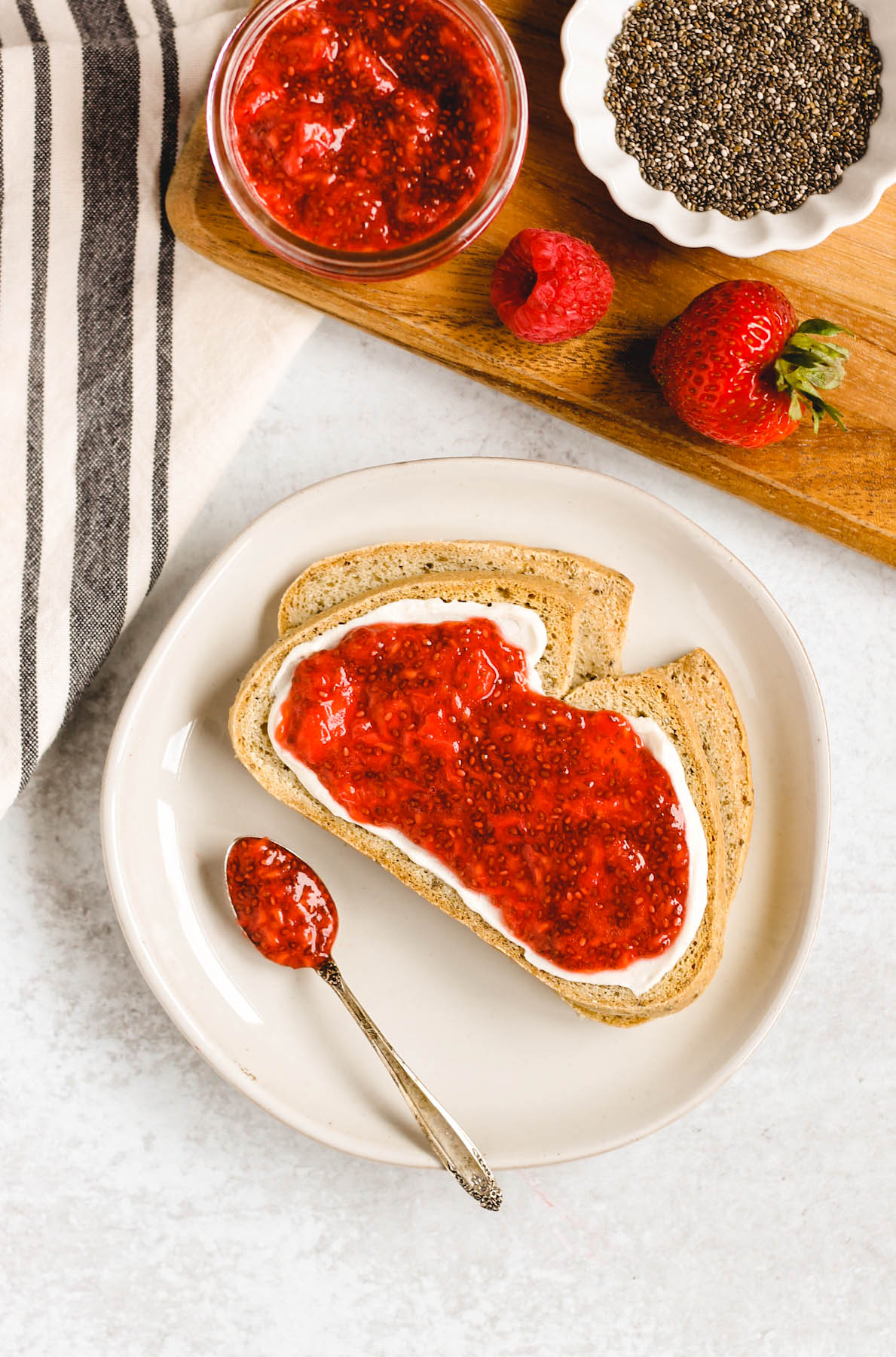 two slices of toast on a plate with cream cheese and berry chia jam spread on toast