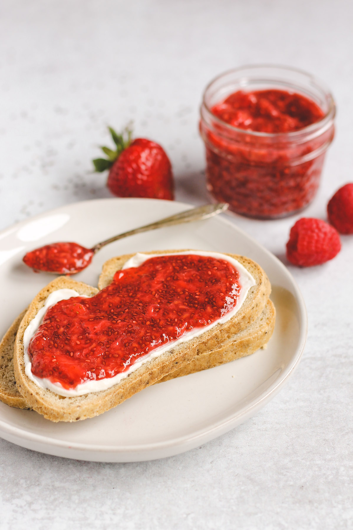 two slices of toast, stacked on top of each other; top toast with cream cheese and jam spread on it