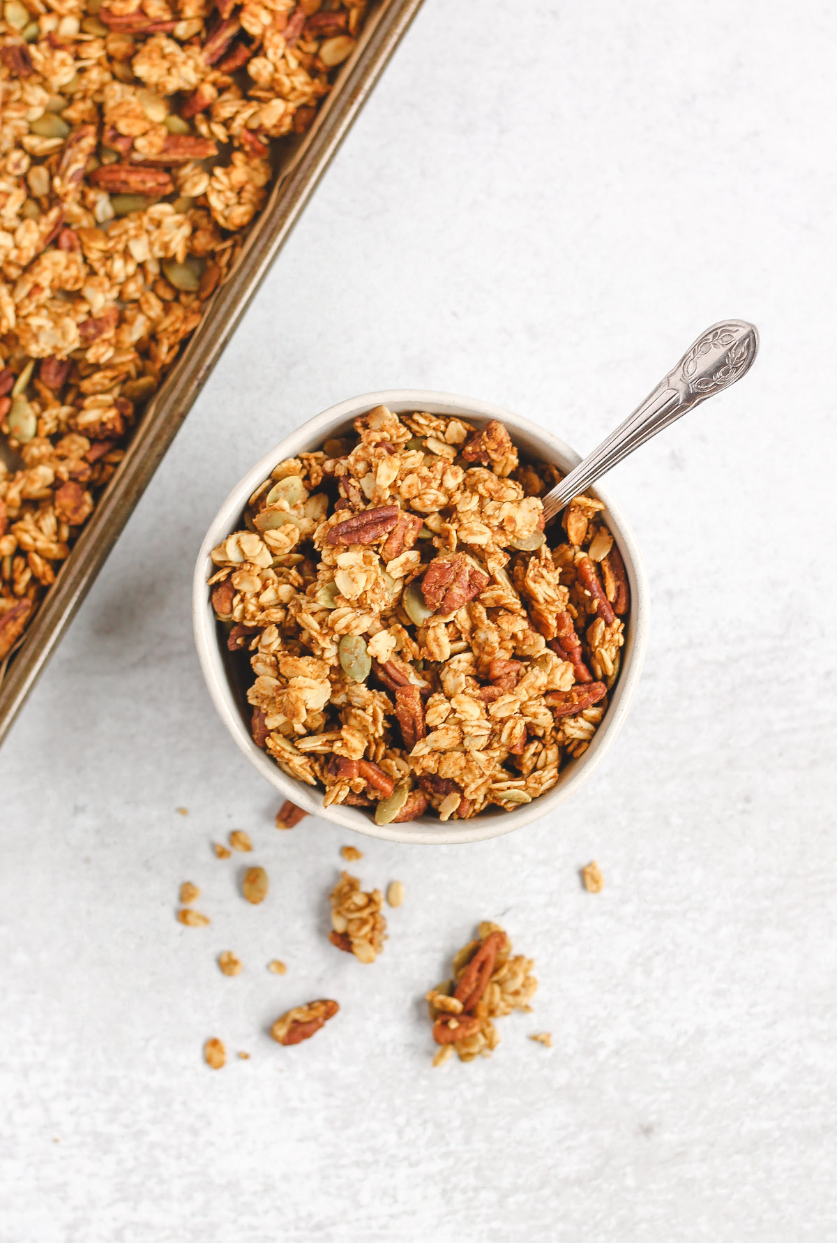 granola in a small white bowl with a silver spoon in bowl