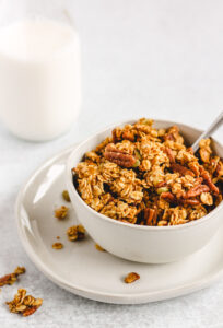 side angle, close up view of pumpkin granola in a small white bowl
