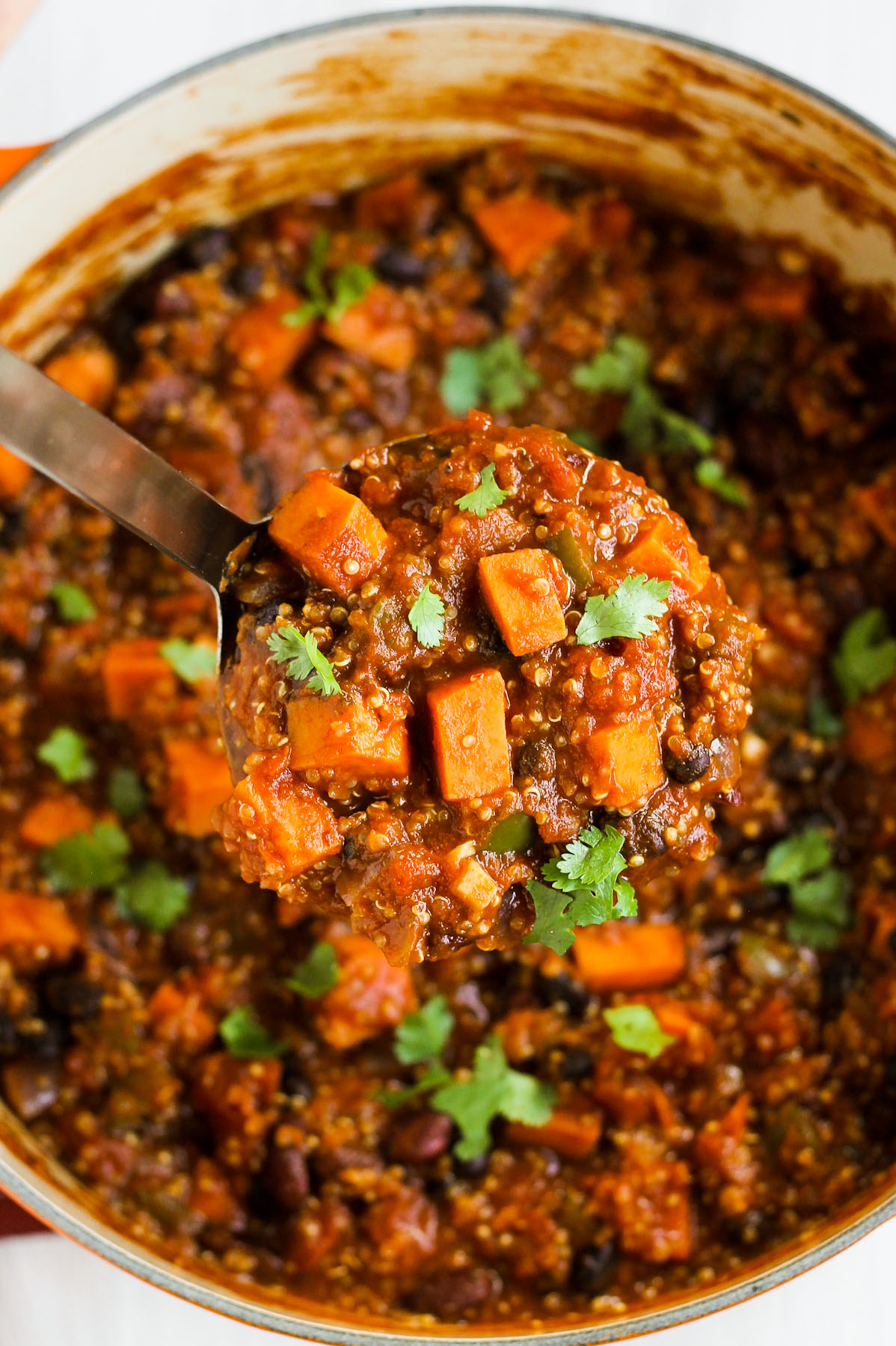 sweet potato chili in a large pot with a big soup ladle scooping some chili out.