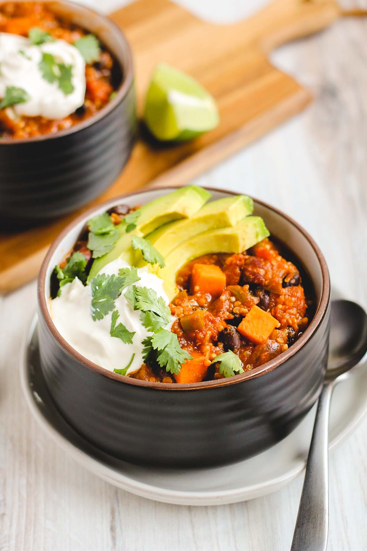 black bowl filled with sweet potato chili topped with sliced avocado, cilantro, and sour cream