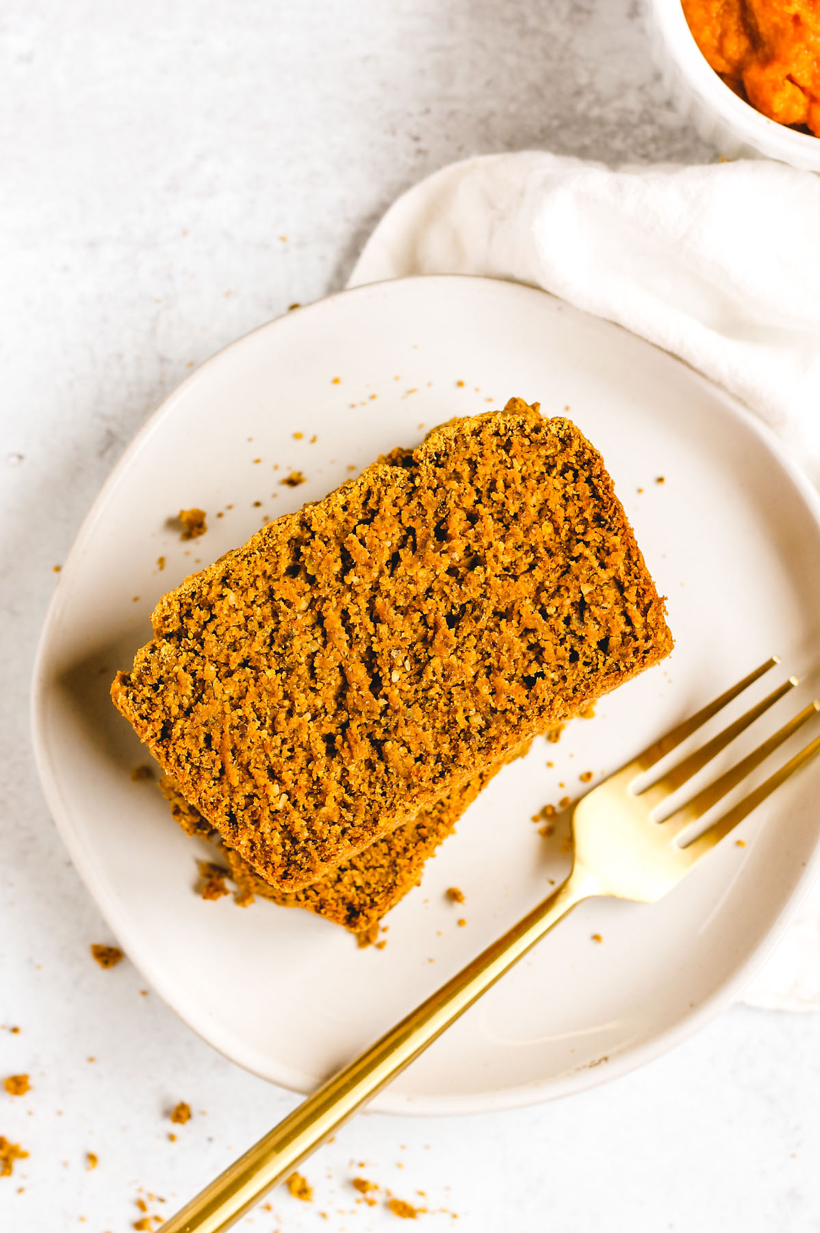 piece of pumpkin bread on a white plate with a gold fork next to the bread
