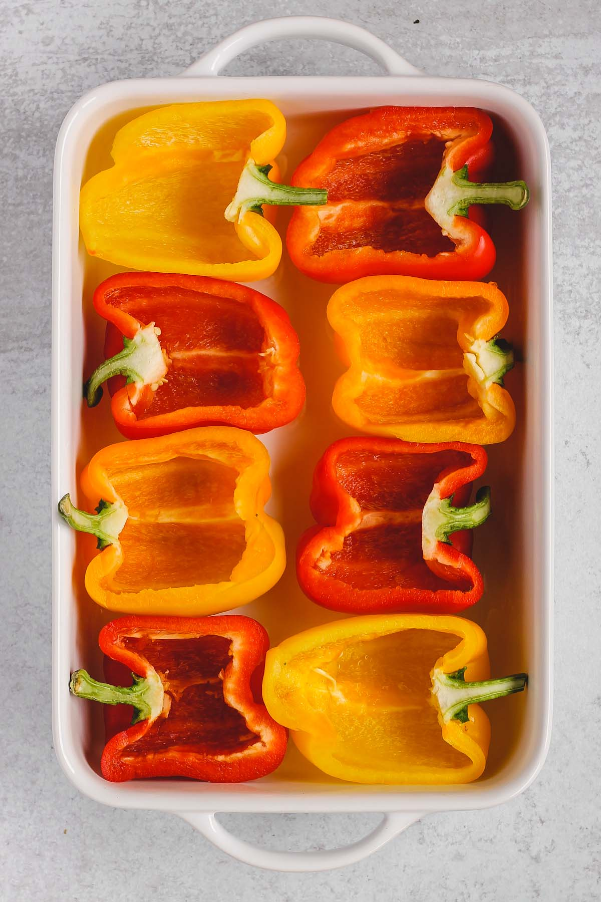 bell peppers cut in half lying in a white baking dish