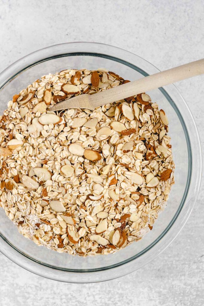 oats, almonds, coconut, and cinnamon in a glass mixing bowl