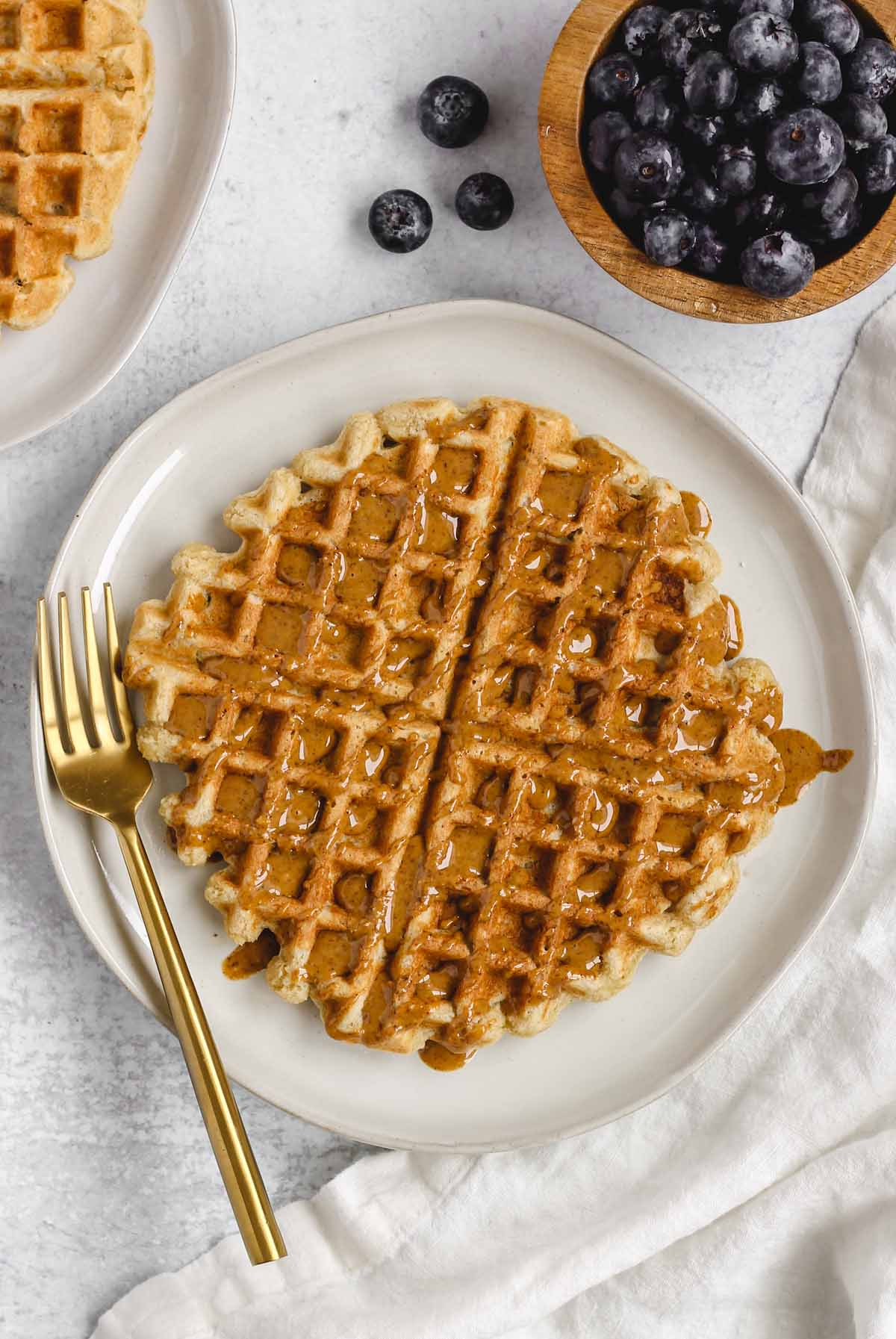 waffle on a white plate drizzled with almond butter with some blueberries in the background