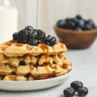 stacked waffles topped with blueberries and blackberries with syrup being poured over