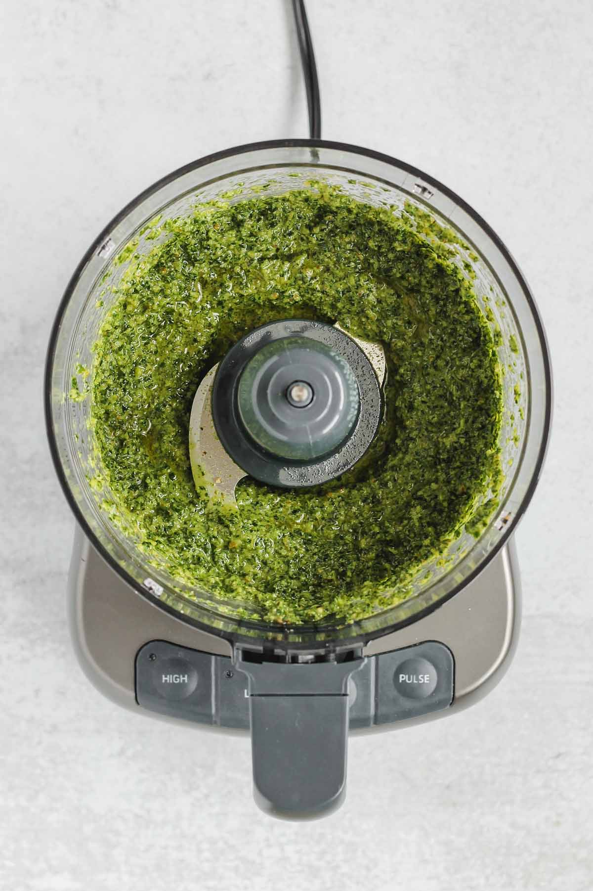 food processor with blended kale pesto sauce