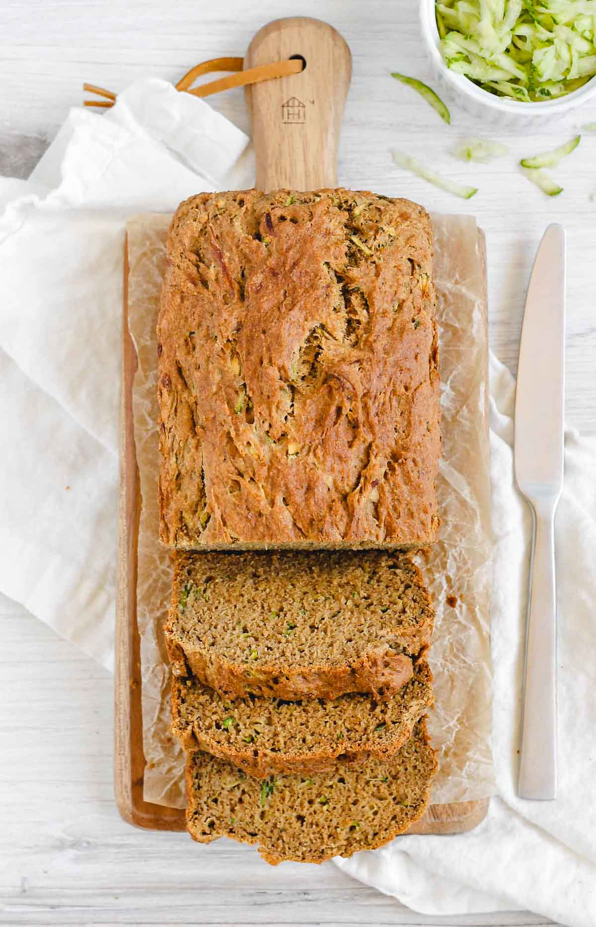 loaf of zucchini bread half sliced on a cutting board